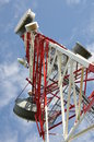 Tower with cell phone antenna system against blue sky Royalty Free Stock Photography