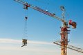 Tower crane lifting up a cement bucket at construction area against blue sky Royalty Free Stock Photography