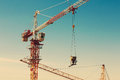 Tower crane lifting up a cement bucket at construction area against blue sky Stock Images