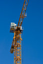 Tower crane yellow against the clear blue sky Royalty Free Stock Photo