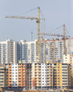 Tower cranes construction city buildings yellow hoisting and residential houses Royalty Free Stock Photography