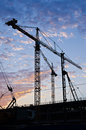 Tower Cranes In Silhouette On Construction Site Royalty Free Stock Images