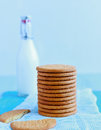 Tower of digestive biscuits along with milk is placed on a blue background Royalty Free Stock Photo