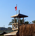 Tower of lifeguard with red flag on the beach Royalty Free Stock Photo