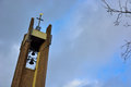Tower of a protestant church and tree tops in clouded sky Stock Photo