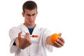 Toxin injection in orange with syringe genetically modified food gmo Royalty Free Stock Photo