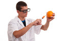 Toxin injection in orange with syringe genetically modified food gmo Stock Photo