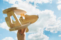 Toy airplane in hand and blue cloudy sky as background. Royalty Free Stock Photo
