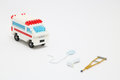 Toy ambulance car, miniature drop, gibbs, and crutch on white background.