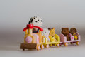 Toy animals sitting on toy train with Stock Photos