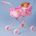Toy baby buggy on blue background. Royalty Free Stock Photo