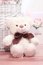 Toy bear is sitting on wicker basket in pink background Stock Photos