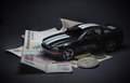Toy car on money, on a black background. Royalty Free Stock Photo
