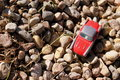 Toy car on the rocks a red sitting warm sunny day for playing outside with toys Royalty Free Stock Images