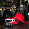 Toy fire truck and real fire truck a firetruck mans hat sit in front of a parked in the denver house in denver colorado Royalty Free Stock Photo