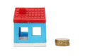 Toy house with coin Royalty Free Stock Images