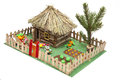 Toy house with thatched roof on green background Stock Image