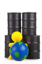 Toy little man sits next on butts to oil the globe world supremacy concept extracting companies Stock Photos