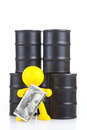 Toy little man stand at butts with oil and holds many money the world supremacy concept oil extracting the companies Stock Images