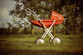 Toy pram in orchard Stock Photo