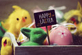 Toy rabbit and chicks, easter eggs and text happy easter