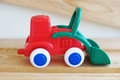 Toy red and green traktor a little with becher white wheels Stock Photography