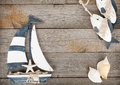 Toy sailboat and fish with seashells on a wooden background Stock Image