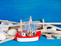 Toy sailboat weathered wood and seashells on blue wood Stock Photography