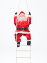 Toy santa climbing a ladder Stock Image