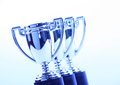 Toy silver trophy cups in a row with a cool blue light effect Stock Photo
