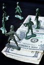 Toy soldier standing with dollar and weapons Royalty Free Stock Images