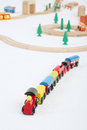 Toy train with cars and wooden toy railway with spruces on white background focus on Royalty Free Stock Photo