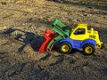 Toy wagon plastic truck with its shadow in sandbox at childrens playground Royalty Free Stock Photo