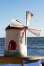 Toy wind mill on boat sailing at sea coast with clear blue sky Stock Photo