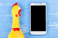 Toy yellow shrilling chicken on blue wooden background with smar Royalty Free Stock Photo