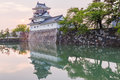 Toyama castle with beautiful sunset and reflection in water. Royalty Free Stock Photo
