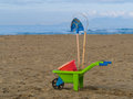 Toys on the beach plastic wheelbarrow, bucket and spade Royalty Free Stock Photo