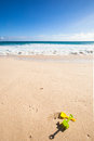 Toys at the beach travel background with a sandy turquoise sea white waves a blue sky and some in sand Royalty Free Stock Photos