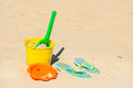 Toys and flip flops at the beach yellow bucket other Stock Images