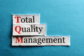 Tqm abbreviation total quality management on blue paper Stock Images
