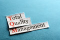 Tqm abbreviation total quality management on blue paper Stock Image