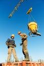 Trabajadores del edificio que vierten el concreto con el barril Imágenes de archivo libres de regalías