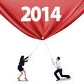 Trabajo en equipo que tira de la bandera del año nuevo de Foto de archivo libre de regalías