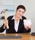 Trabalhador de escritório de sorriso que quebra um banco piggy Imagens de Stock