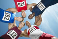 Track and field athletes forming huddle against sky directly below shot of multiethnic Stock Photos