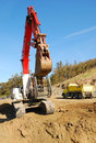 Track hoe large exchavator working a dirt pile at a new commercial construction site in roseburg oregon Stock Photo