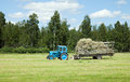 Tractor doing farm works at summer time collecting food for the animals for winter season Royalty Free Stock Images