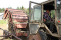 Tractor-driver operates from the tractor hitches round hay baler Royalty Free Stock Photo