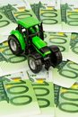 Tractor on euro banknotes a standing symbolic photo for costs revenues and subsidies a farmer in agriculture Royalty Free Stock Photo