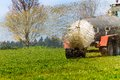 Tractor fertilizes with manure a field in autumn Royalty Free Stock Photo